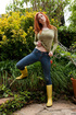 Hot ginger damsel posing in lingerie and rubber high boots in the garden