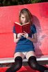 Leggy teen with braids in stockings reading outdoors
