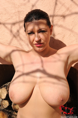 Very busty brunette beauty is tied spread eagled outdoors along the wall of a house and had no qualms about pissing right there - XXXonXXX - Pic 1