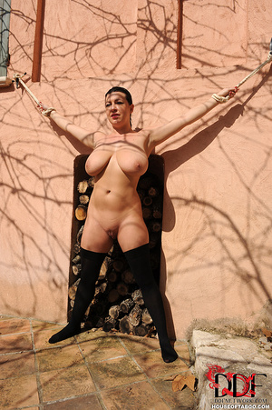 Very busty brunette beauty is tied spread eagled outdoors along the wall of a house and had no qualms about pissing right there - XXXonXXX - Pic 3