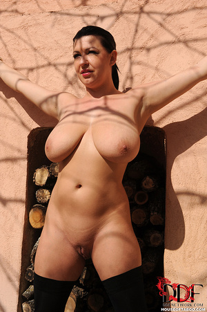 Very busty brunette beauty is tied spread eagled outdoors along the wall of a house and had no qualms about pissing right there - XXXonXXX - Pic 4