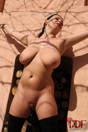 Very busty brunette beauty is tied spread eagled outdoors along the wall of a house and had no qualms about pissing right there - XXXonXXX - Pic 5