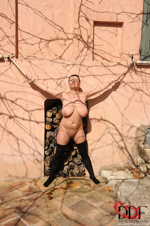 Very busty brunette beauty is tied spread eagled outdoors along the wall of a house and had no qualms about pissing right there - XXXonXXX - Pic 7