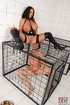 Busty brunette dom cages a naked man sub then she pisses over sub on the
