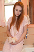 Sultry ginger vixen in a long lace gown posing in the bathroom
