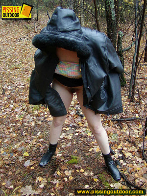 Shy teen wrapped up in a hooded black coat bends down to piss freely in the woods - XXXonXXX - Pic 4