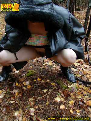 Shy teen wrapped up in a hooded black coat bends down to piss freely in the woods - XXXonXXX - Pic 9