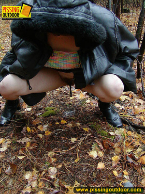 Shy teen wrapped up in a hooded black coat bends down to piss freely in the woods - XXXonXXX - Pic 11