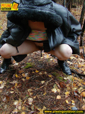 Shy teen wrapped up in a hooded black coat bends down to piss freely in the woods - XXXonXXX - Pic 12