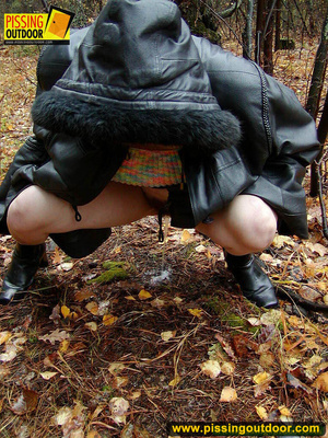 Shy teen wrapped up in a hooded black coat bends down to piss freely in the woods - XXXonXXX - Pic 17