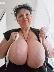 Curly brunette mature playing with her giant titties - Picture 12