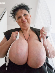Curly brunette mature playing with her giant titties - Picture 13