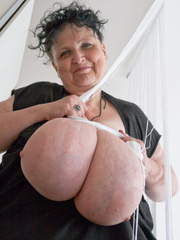 Curly brunette mature playing with her giant titties - Picture 15