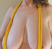 Busty goddess topless having fun with a yellow rope