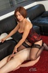 Red hottie in a corset sitting on masked dude's face