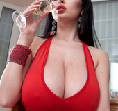 Young and sexy brunette in red dress showes off her amazing tits while