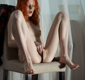 Redhead in a black sweater and black lingerie fingers on a chair.