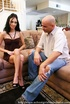 Bald guy bangs a slender brunette on a brown couch.