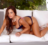 Amateur in a purple bra and thong poses on a white leather seat in the