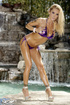Hot bombshell posing her stunning oiled body in purple stringed bikini