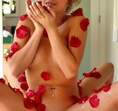 Lady in a tub with rose petals all over her body cannot  conceal the steamy
