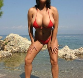 Hot cute brunette in tiny red bikini cools her gigantic boobs in the lake
