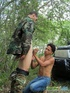 Military man in camo uniform does it with a civilian guy in the woods.