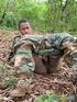Gentleman in battle dress uniform lays down on fallen leaves to display