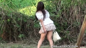 Cute Asian in sexy short skirt pressed on the streets hides to pee behind bench - XXXonXXX - Pic 2