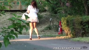 Cute Asian in sexy short skirt pressed on the streets hides to pee behind bench - XXXonXXX - Pic 3