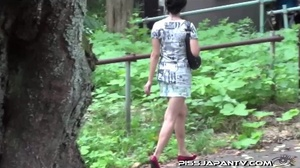 Slim Asian babe in tight jeans skirt bends twice to piss outdoors and wets self - XXXonXXX - Pic 1
