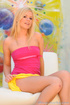 Adorable fledgling in a pink top and yellow skirt kneels on a red rug