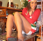 Girl in white short with red top and heels poses seductively in the study