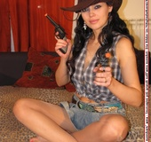 Cowgirl in blue short and brown boxed top with grey boots pose on a leopard