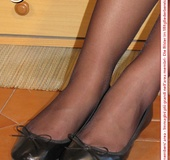 Young tall temptress in black dress, black pantyhose and shoes displays