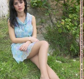 Chick in a blue dress shows off her stockinged feet in the garden.