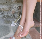 Lass takes off her white strappy heels to show her bare feet.