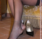 Madam in black heels and fishnets displaying her legs and feet.
