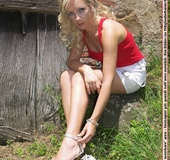 Blonde minx takes off her white heels near the door.