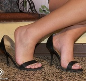 Nymph takes off her peep toe heels in front of the fireplace.