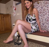 Firecracker in black sandals exposes her bare feet in front of the fireplace.