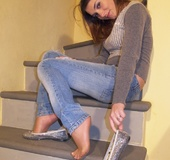Girlie removes her shimmering flats to show her feet covered with stockings.