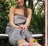 Alluring broad on a white bench showing off her red painted toe nails.