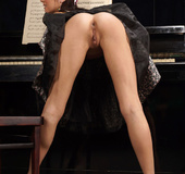 Strumpet in a flowery dress gets naked by the piano.