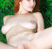 Tender trick sheds her red lingerie in a grassy clearing.