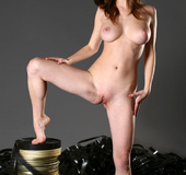 Marvelous senora wrapped in film reels sits naked on the film cans.