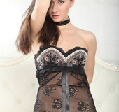Charming dish in a sheer black nightie displays her shaved snatch in bed.