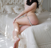 Fox in white lingerie with black trim shows off her slick slit in bed.