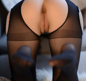Gorgeous filly in black lingerie and stockings gets naked in the living
