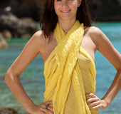 Yummy girl in a yellow wrap displays her poon at the beach.